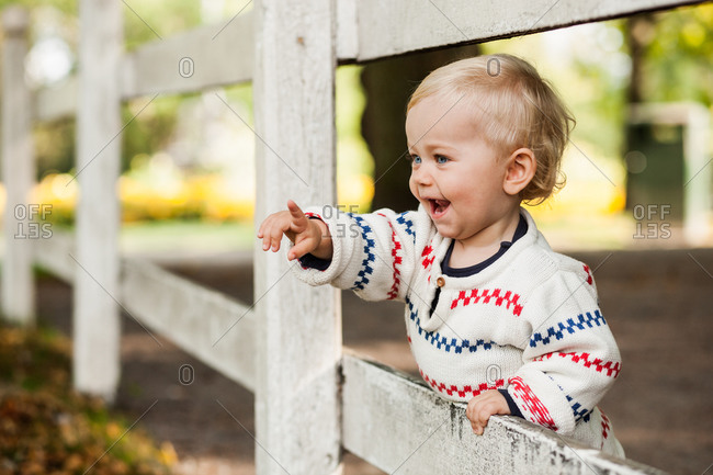 Happy baby girl pointing while standing by wooden fence in park