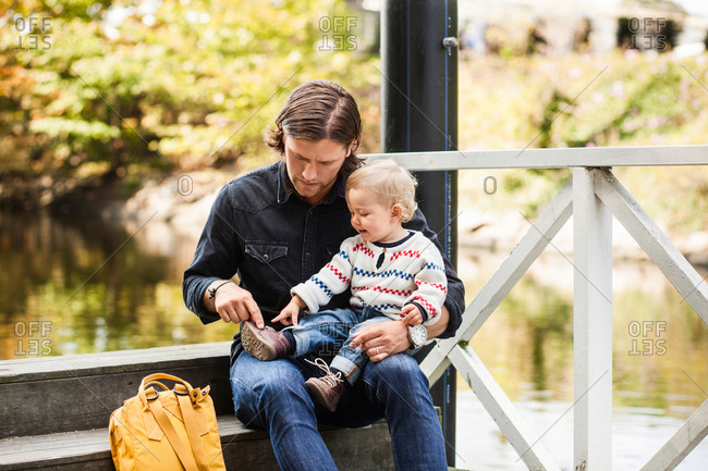 Baby girl showing shoe to father while sitting on steps at lakeshore