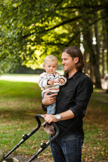 Smiling man holding baby carriage while carrying daughter in park