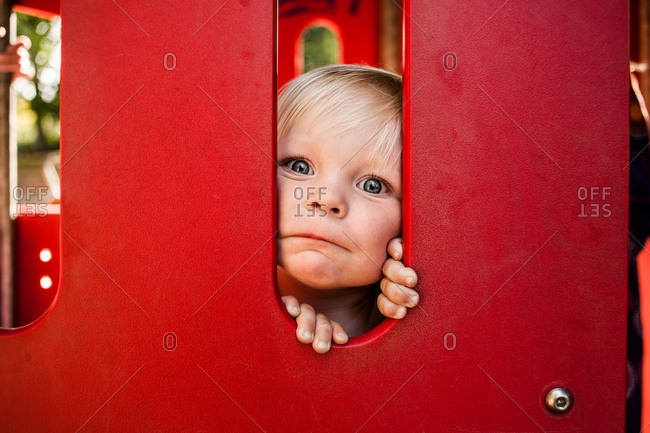 Portrait of baby boy peeking through red playing equipment in park