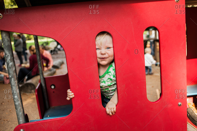 Portrait of happy baby boy peeking through red playing equipment in park