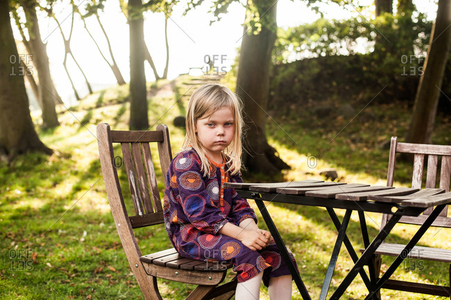 Sad girl sitting at wooden table in park