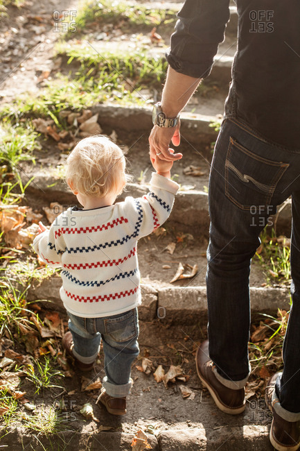 Rear view of father and daughter holding hands while climbing steps in park