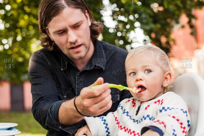 Young man feeding baby girl at park
