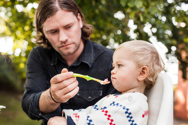 Father feeding angry daughter in park