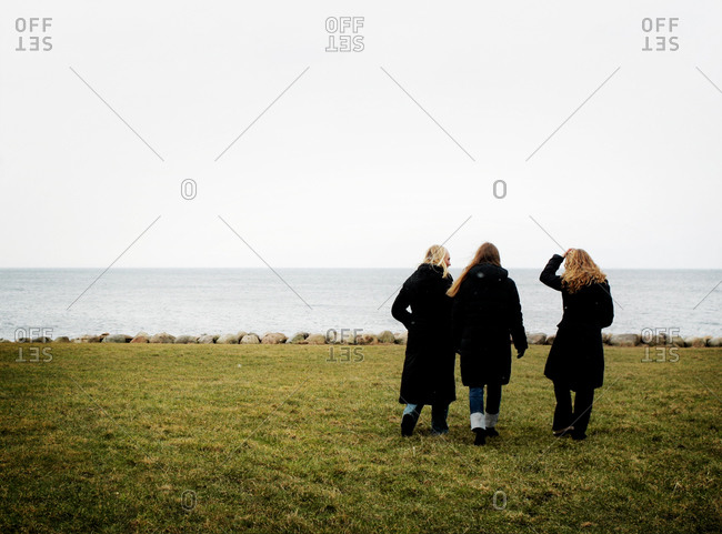 Three girls going for a walk by the coast
