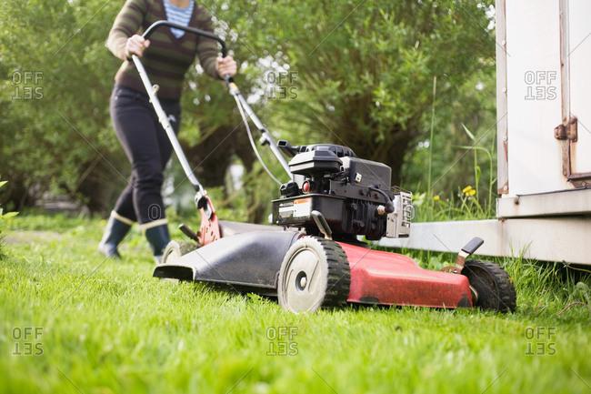 Women pulls a lawnmower
