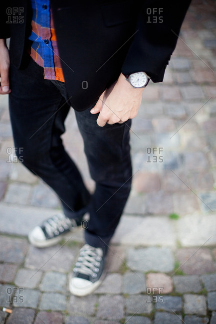 Low section of  man with black jeans and canvas shoe