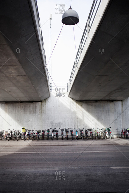 Large group of bicycles parked under elevated road