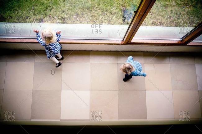 Playful girls looking through window