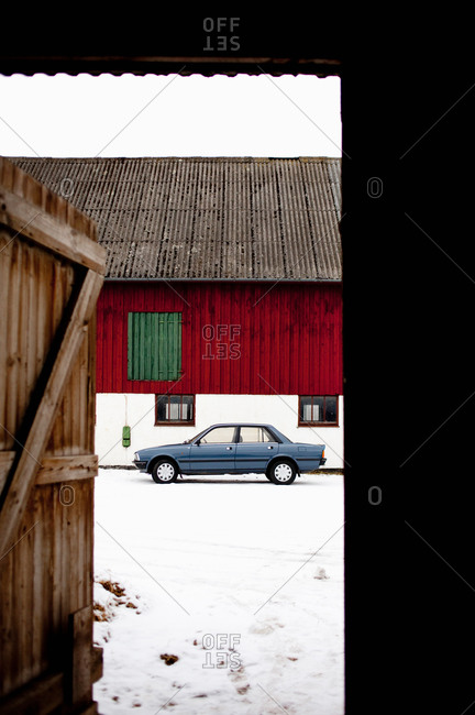 Car on snowcapped landscape in front of house
