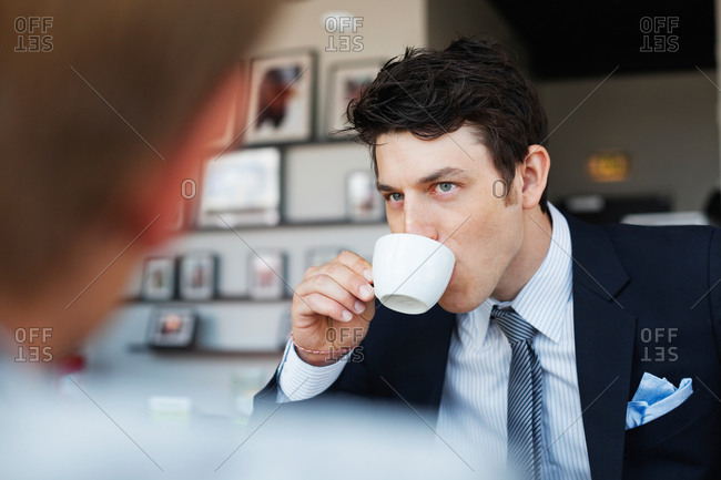 Young businessman having coffee while looking at colleague