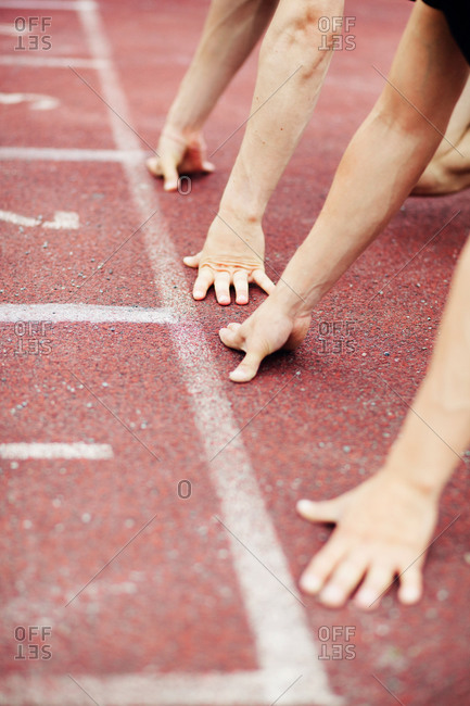 Hands at the starting line of running track