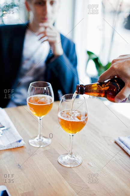 Hand pouring beer in glass with man sitting at restaurant