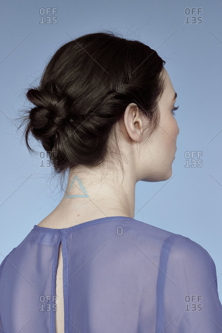 Portrait of a woman with a triangle tattoo on her neck