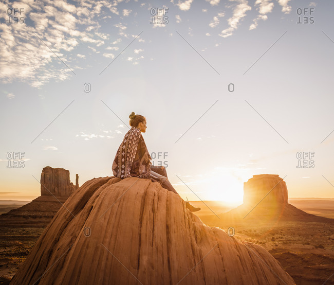 Woman sitting on rock formation in remote desert