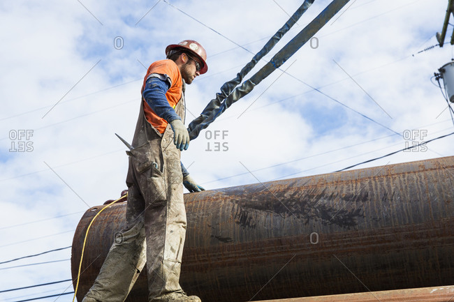 Worker hauling pipe at construction site