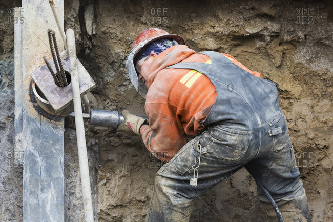 Worker drilling at construction site