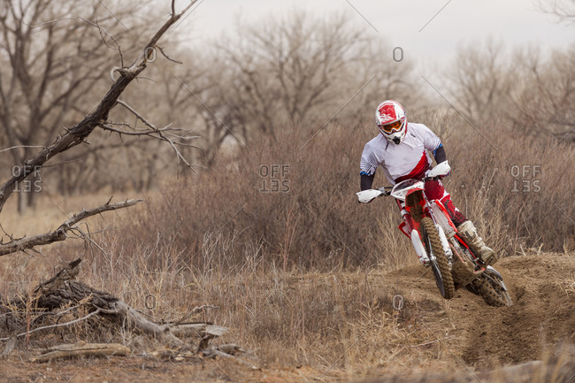 Motorcyclist riding dirt bike on rural path