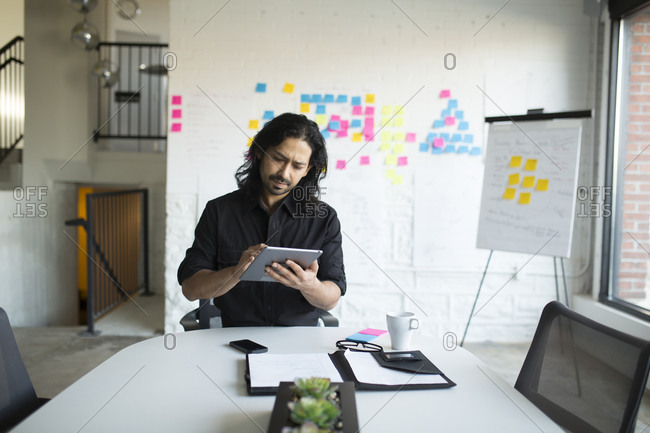 Mixed race businessman using digital tablet in office