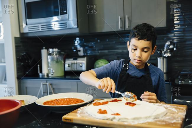 Boy making pizza in kitchen