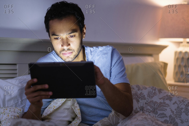 Man using digital tablet in bed