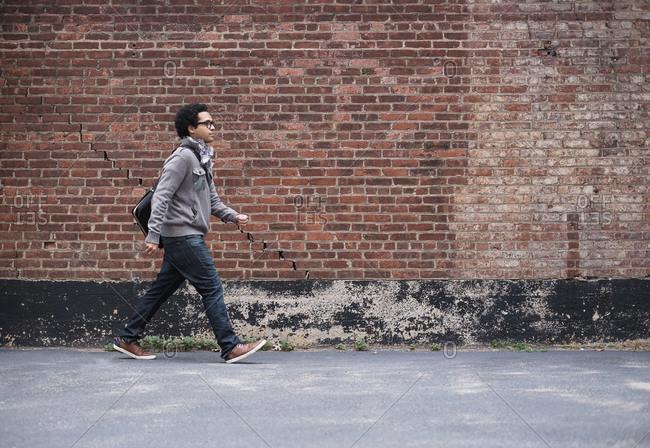 Man walking near brick wall