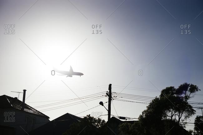 Airplane flying over neighborhood rooftops