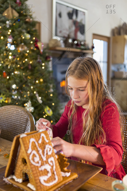 Girl decorating gingerbread house