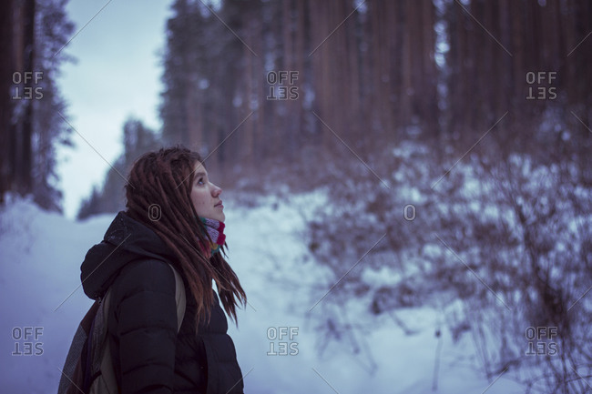 Woman standing in snowy forest