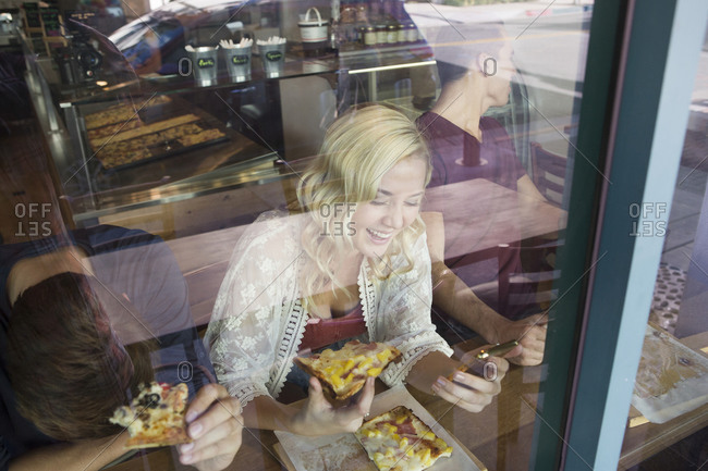 Woman eating pizza in cafe