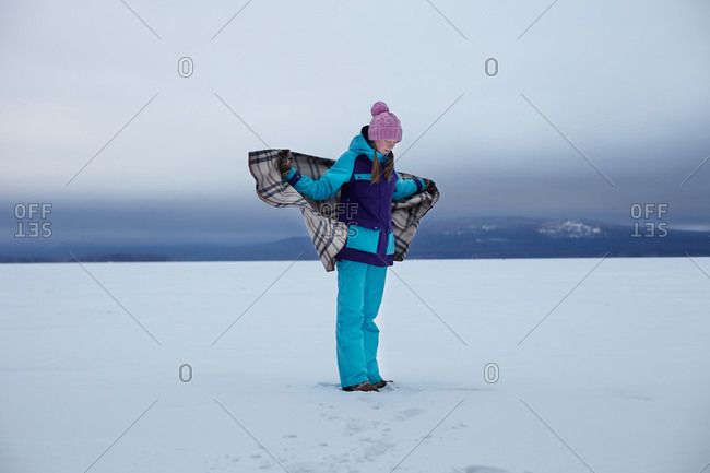 Teenage girl wrapped in blanket in snow