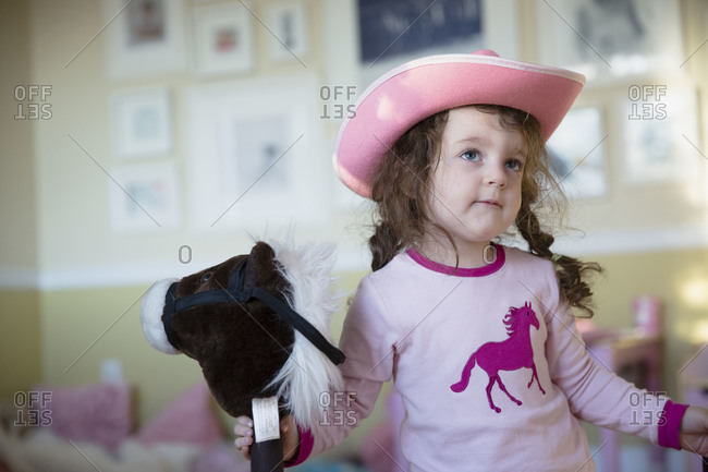Portrait of a young girl wearing a cowboy hat and playing with a hobby horse