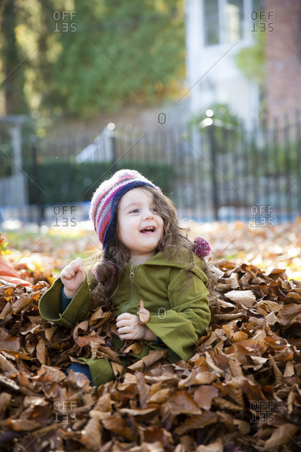 Young girl sitting outside in a pile of leaves