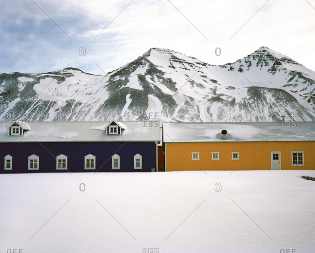 Colorful buildings surrounded by snow at the base of a mountain in Siglufjörður, Iceland