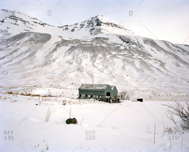 Abandoned wood structure surrounded by snow and tundra at the base of a mountain in Siglufjörður, Iceland