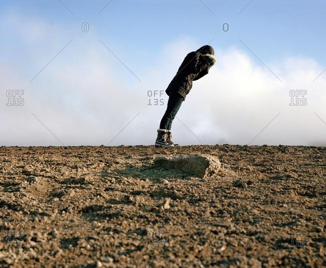 Woman leaning forward into a strong wind in Siglufjörður, Iceland
