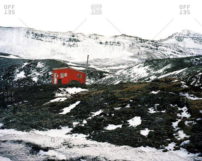 Colorful red building surrounded by snow at the base of a mountain in Siglufjörður, Iceland