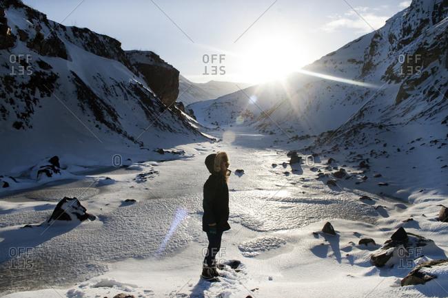 Woman standing in a snowy valley in Siglufjörður, Iceland