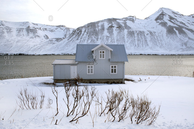 Small house surrounded by snow at the edge of the water in Siglufjörður, Iceland