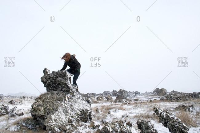 Woman climbing a stone boulder in Siglufjörður, Iceland