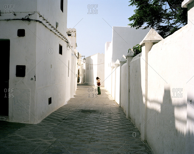Woman standing along a narrow street in Fez, Morocco