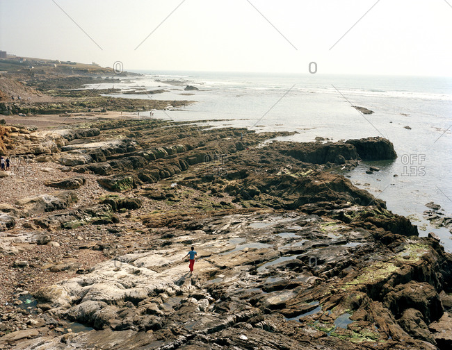 Aerial view of a young boy running along a rocky beach in Morocco
