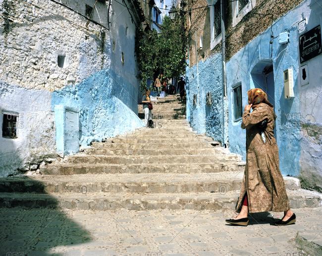 Woman walking along a narrow street in Fez, Morocco