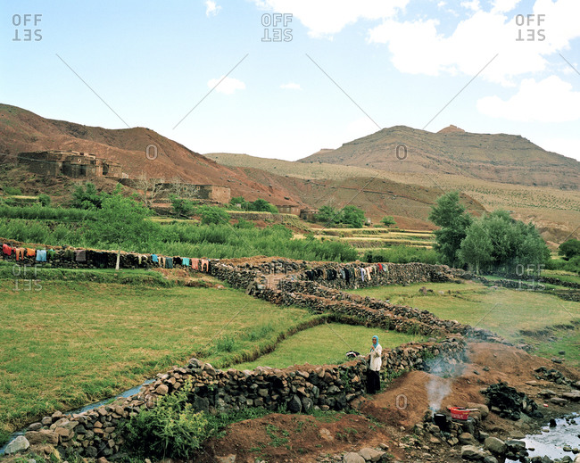 Sahara Desert, Morocco - June 18, 2010: Woman standing along a stone fence in Morocco