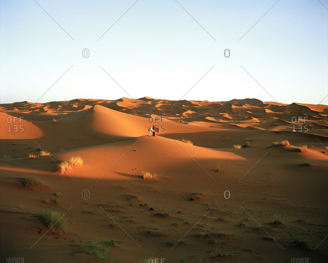 Two people holding shawls standing in the Sahara Desert in Morocco