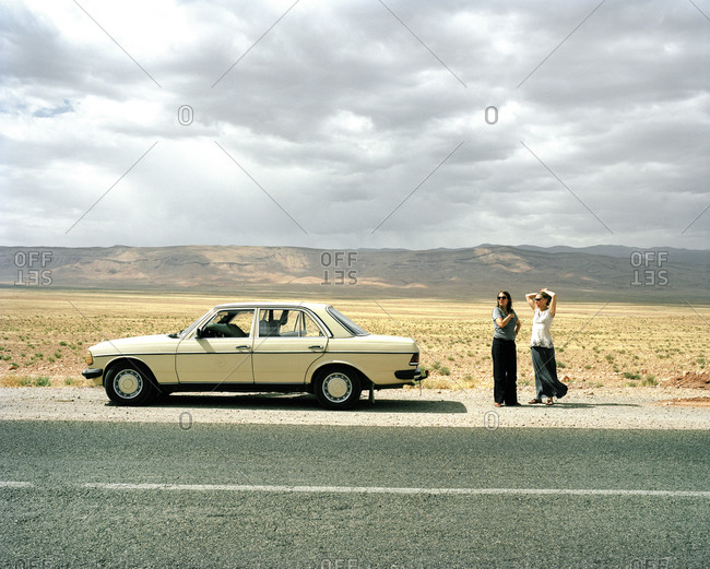 Two women standing behind a parked car on a road in the Sahara Desert in Morocco