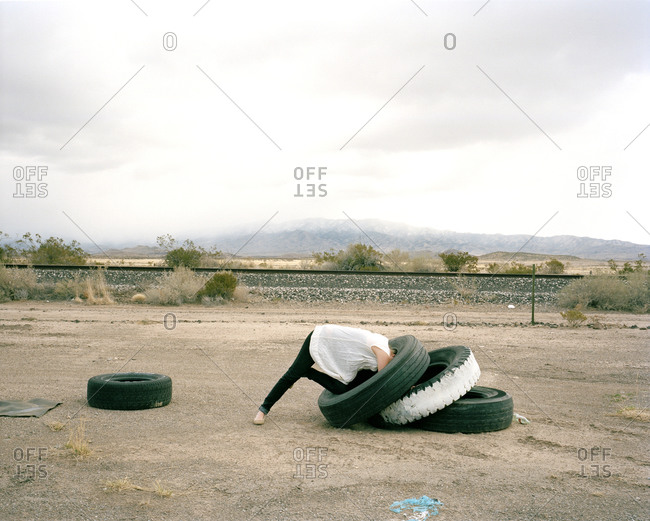 Woman playing with tires in a vacant dirt lot in White Sands, New Mexico