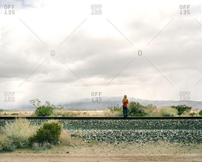 Woman standing along railroad tracks in White Sands, New Mexico