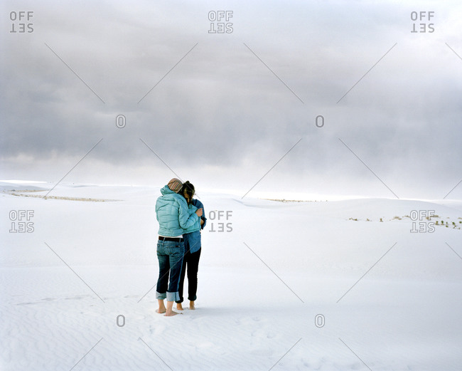 Two women embracing in the desert in White Sands, New Mexico